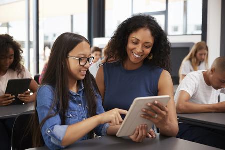 Profesor ayudando a colegiala adolescente con tableta