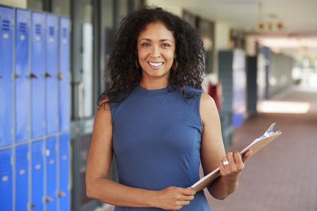 W średnim wieku czarny żeński nauczyciel ono uśmiecha się w szkolnym korytarzu