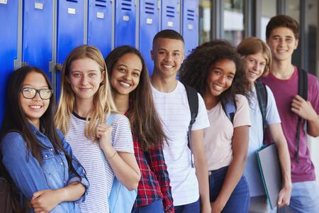 Nastoletnie dzieci w wieku szkolnym uśmiecha się do kamery w szkolnym korytarzu