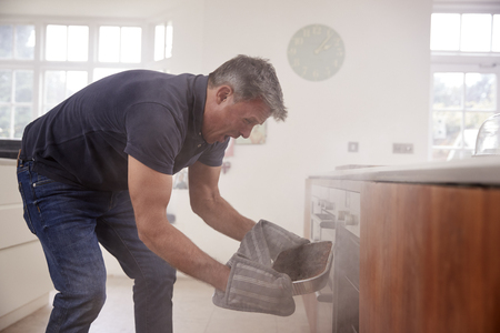 Middle aged man opening smoke filled oven in the kitchen Reklamní fotografie