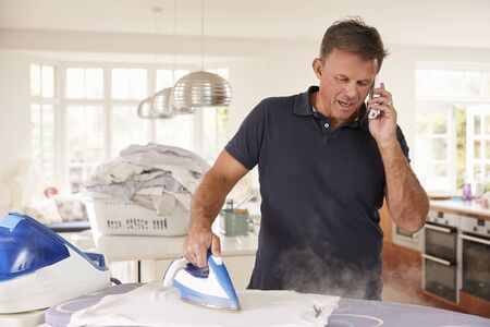 Middle aged man distracted by phone while ironing Reklamní fotografie