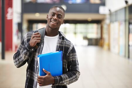 Portrait Of Male Student Standing In College Building Foto de archivo