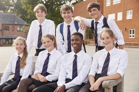 Retrato de estudiantes adolescentes en uniforme fuera de los edificios escolares