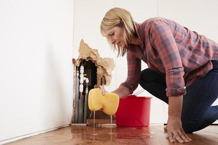 Donna preoccupata che asciuga l'acqua da un tubo di scoppio con una spugna Archivio Fotografico - 91579759