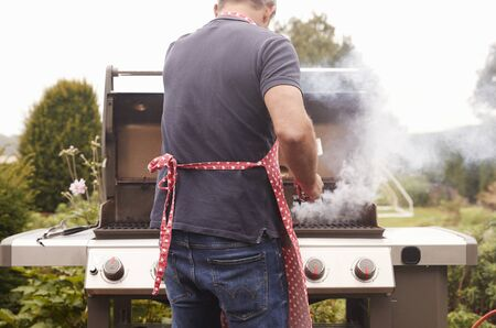 Middle aged man burning food on a barbecue, back view Stock Photo