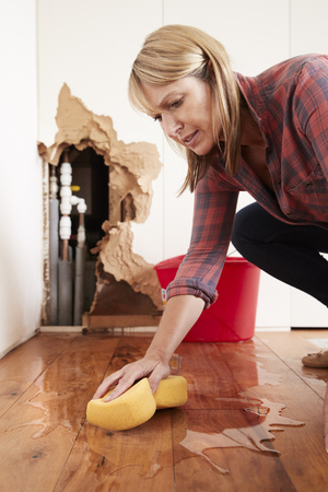 Woman mopping up water from a burst pipe with sponge, vertical