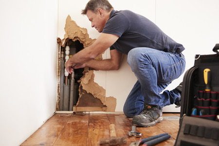Middle aged man repairing burst water pipe