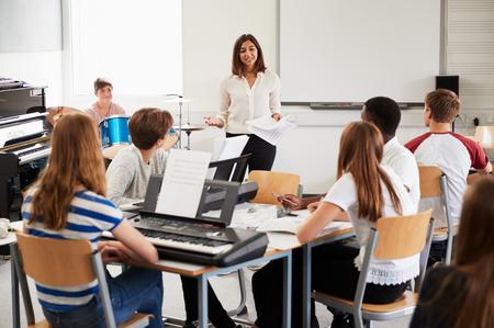 Tiener Studenten Studeren In Muziek Klasse Met Vrouwelijke Leraar Stockfoto