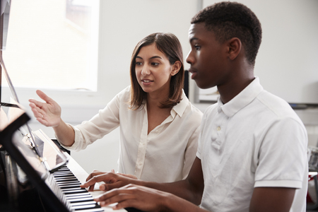 Male Pupil With Teacher Playing Piano In Music Lesson Stock Photo - 91651263