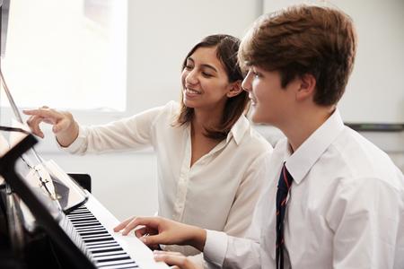 Mężczyzna Uczeń Z Nauczycielem Gry Na Fortepianie W Lekcji Muzyki Zdjęcie Seryjne