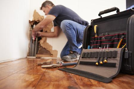 Mężczyzna w średnim wieku naprawy pęknięcia rury, hydraulika, skupić się na pierwszym planie