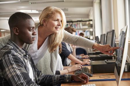 enseignant avec un étudiant mâle travaillant sur ordinateur dans la bibliothèque du collège