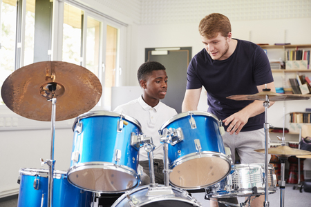 음악 수업에서 드럼을 연주하는 교사와 함께 남성 학생