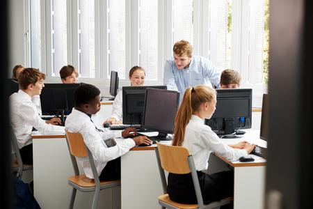 Estudiantes adolescentes con uniforme estudiando en clase de informática Foto de archivo