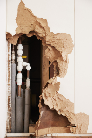 Beschadigde muur die gebarsten waterpijpen na verticale vloed blootstelt