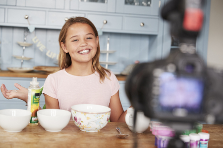 Pre-teen girl video blogging in the kitchen smiles to camera