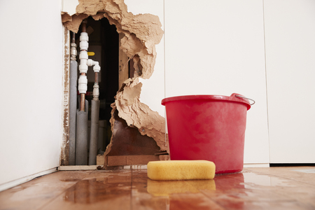 Damaged wall, exposed burst water pipes, sponge and bucket