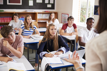 Students Listening To Female Teacher In Classroom