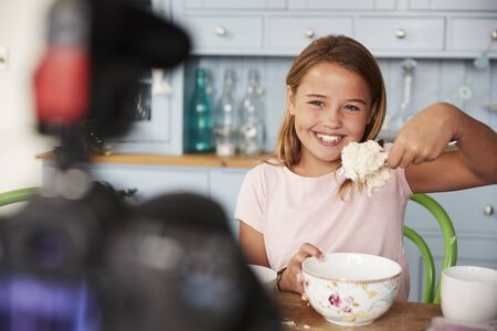 Young girl video blogging in kitchen showing spoon of dough