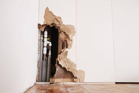 홍수 후 버스트 급수관이 노출 된 손상된 벽