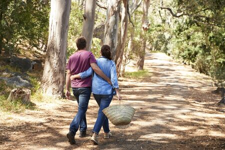 Rear View Of Romantic Couple Hiking Along Forest Path Reklamní fotografie