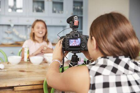 Girl filming her friend for cookery video blog in kitchen Reklamní fotografie