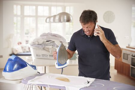 Middle aged man distracted by phone when ironing burns shirt Reklamní fotografie