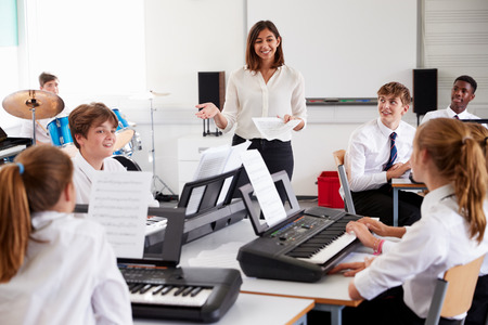 Teenage Students Studying Electronic Keyboard In Music Class Stockfoto