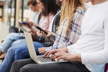 Close Up Of Seated College Students Using Digital Technology