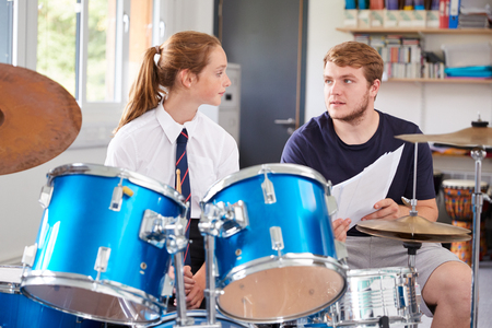 Female Pupil With Teacher Playing Drums In Music Lesson Stok Fotoğraf