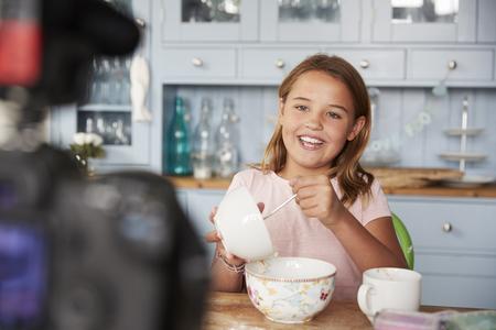 Pre-teen girl video blogging in kitchen mixing ingredients