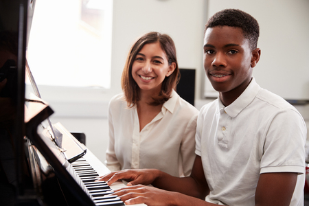 Portrait Of Pupil With Teacher Playing Piano In Music Lesson Foto de archivo