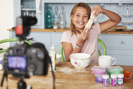 Young girl video blogging in a kitchen showing dough mixture