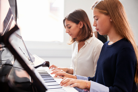 Female Pupil With Teacher Playing Piano In Music Lesson Stock Photo - 91580487