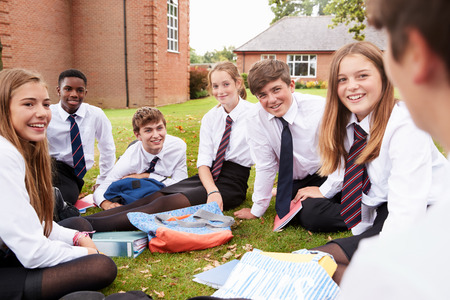 Teenage Students In Uniform Working On Project Outdoors Foto de archivo