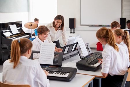 Teenage Students Studying Electronic Keyboard In Music Class Stock Photo