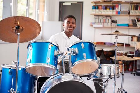 Mannelijke tienerleerling het spelen drums in muziekles Stockfoto