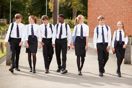 Grupo de estudantes adolescentes em uniforme fora dos edifícios escolares Foto de archivo - 91940501