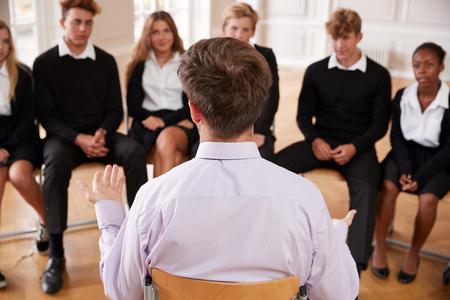 교사와 함께 이야기하는 십대 학생들의 그룹