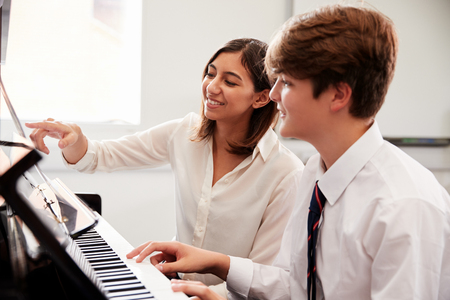 Male Pupil With Teacher Playing Piano In Music Lesson