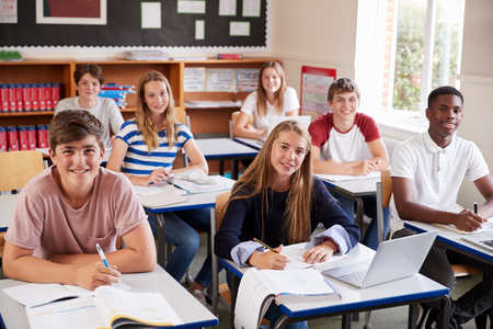 Portrait Of Students Sitting At Desks In Classroom