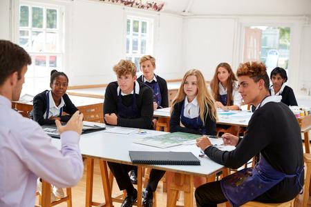 Tienerstudenten die aan Leraar In Art Class luisteren Stockfoto