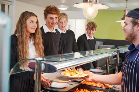 Studenti adolescenti che sono serviti pasto nella mensa scolastica Archivio Fotografico - 91940569