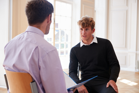 Estudiante adolescente masculino que tiene discusión con el tutor Foto de archivo - 91940575