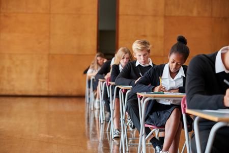 学校ホールで制服座り試験を受けた十代の学生