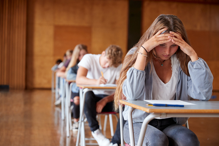 Anxious Teenage Student Sitting Examination In School Hall Standard-Bild