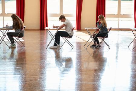 Gruppo di studenti adolescenti che si siedono esame nel corridoio della scuola Archivio Fotografico