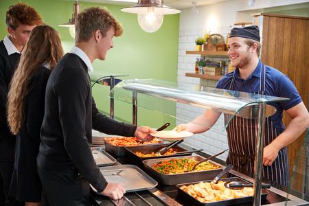 Teenage Studenten serviert Mahlzeit in der Schule Kantine Standard-Bild