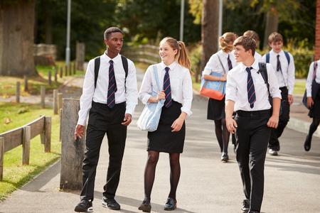 Grupo de estudiantes adolescentes en edificios uniformes fuera de la escuela