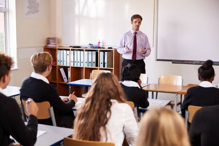 Teenage Students Listening To Male Teacher In Classroom Stock Photo